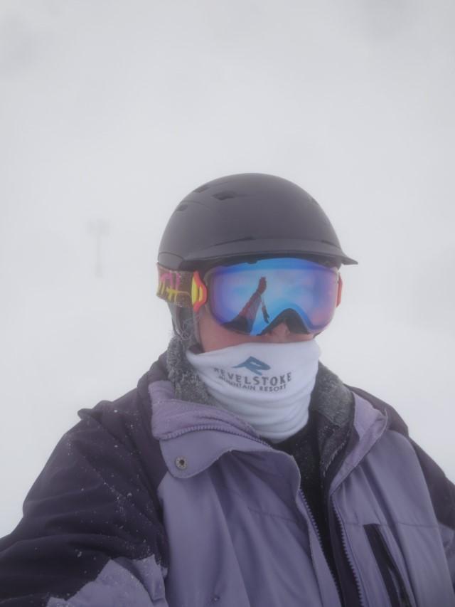 skier in a purple coat in on a foggy day