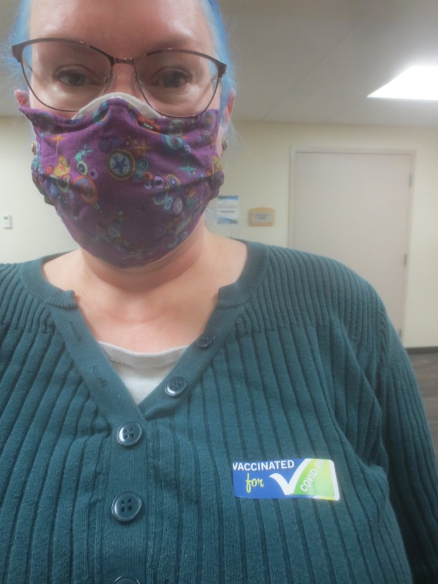 white woman wearing glasses and two masks with a COVID-19 vaccination sticker on her shirt