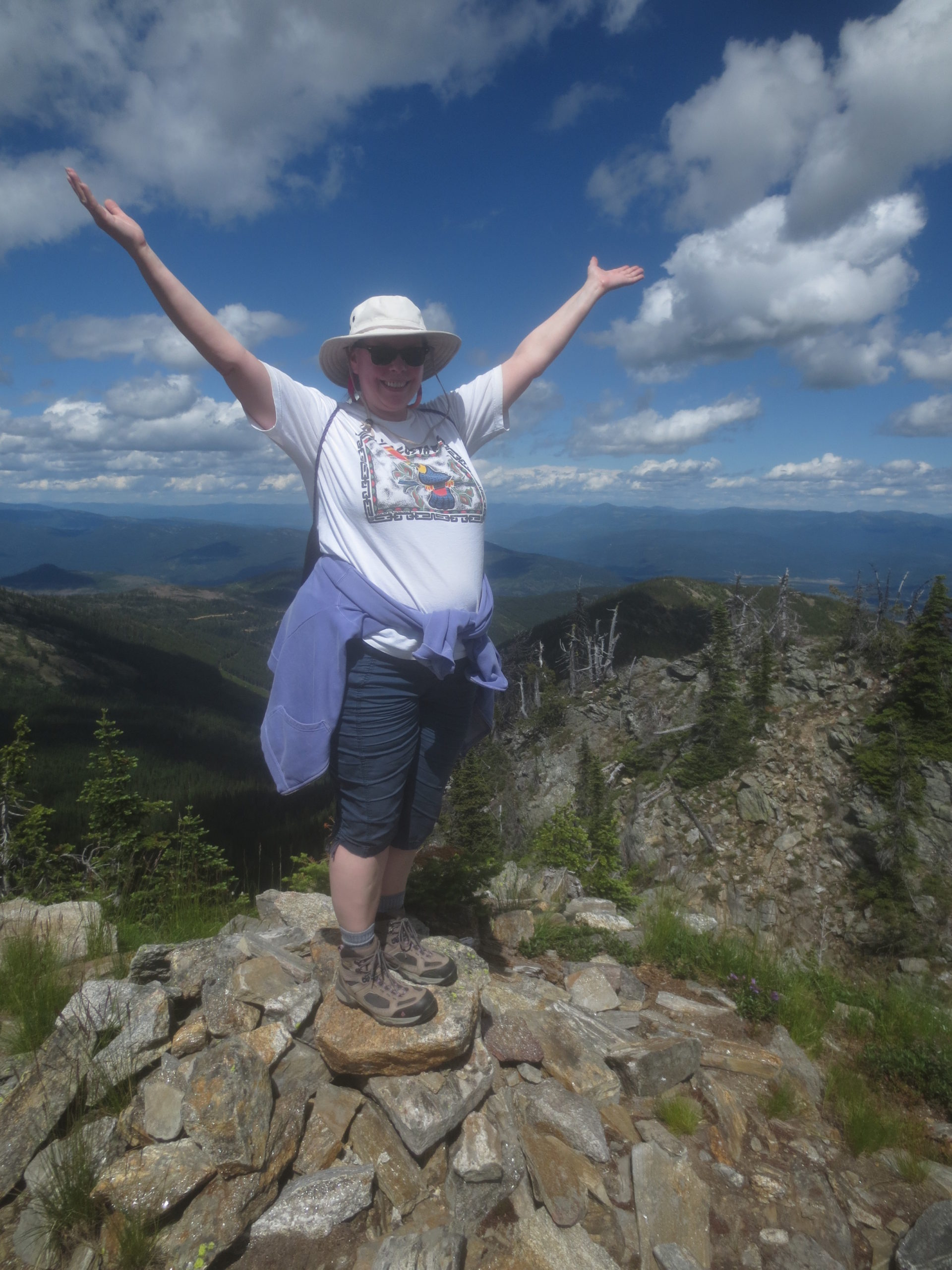 woman with arms raised in celebration at the top of a mountain