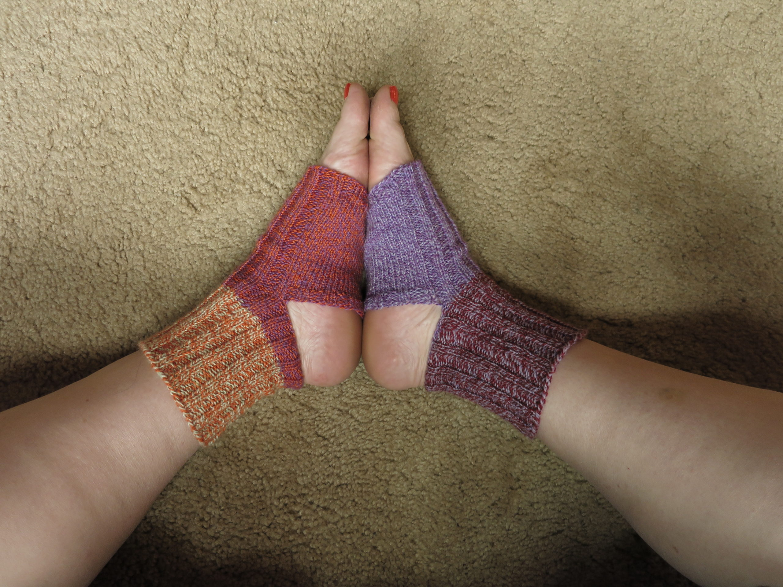 hand knit yoga socks in purples, orange, dark red, and tan