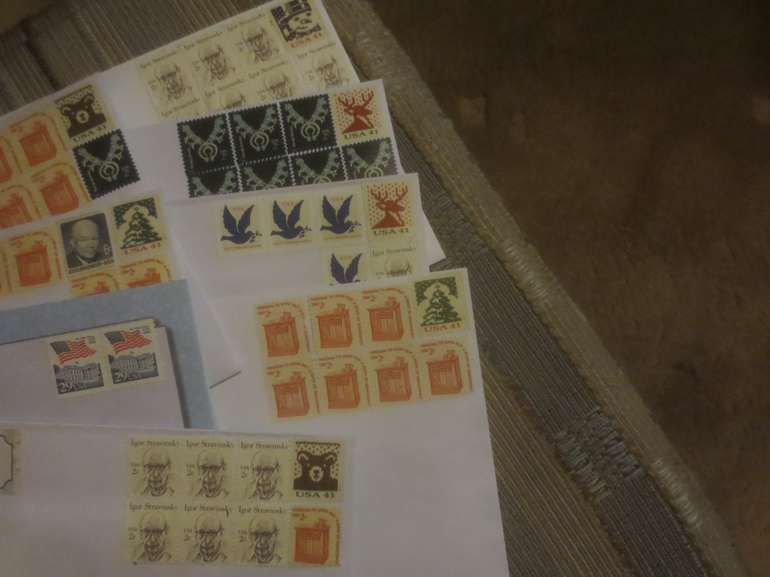 Corners of envelopes laid out on a fabric background with various combinations of stamps on them