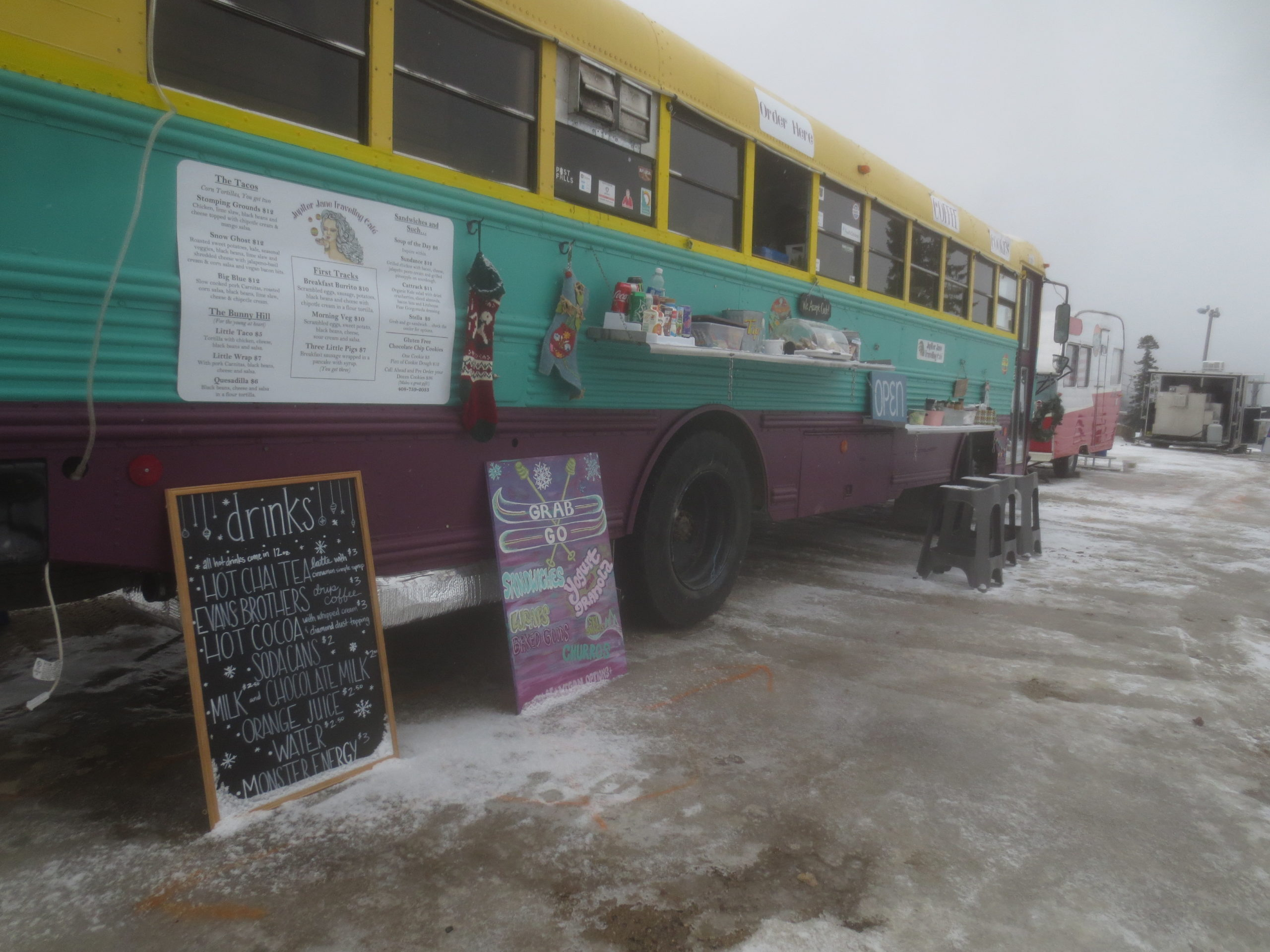 former school bus painted purple and teal and in use as a food truck
