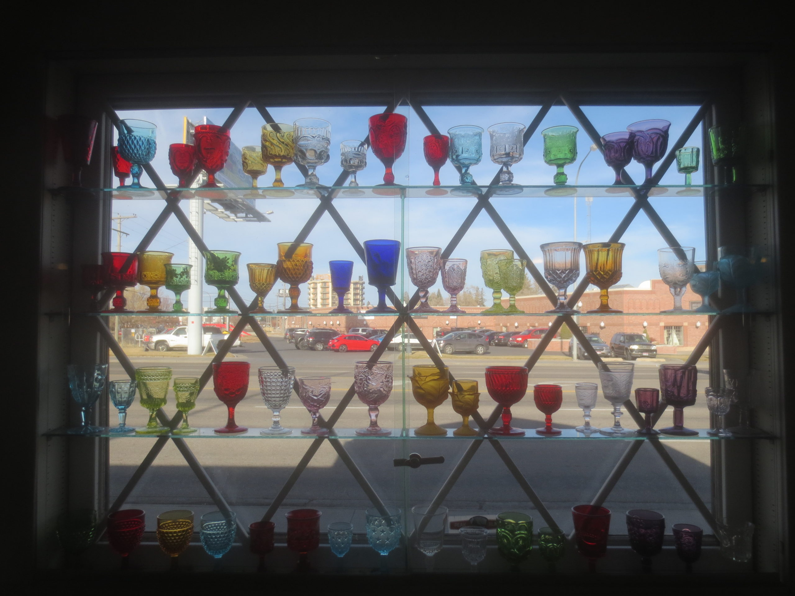 colorful glassware on shelves in front of a window