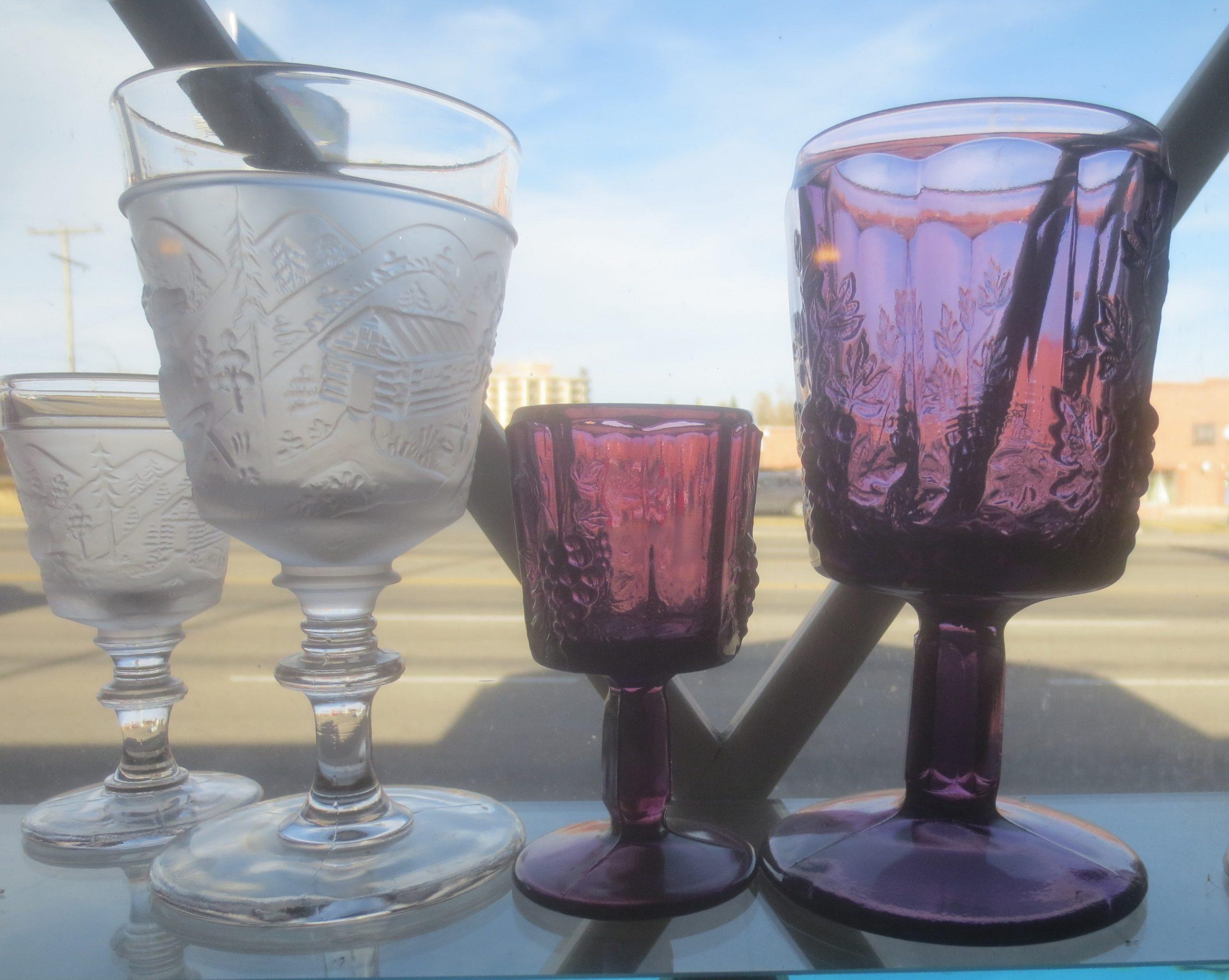 four decorative glasses in a window