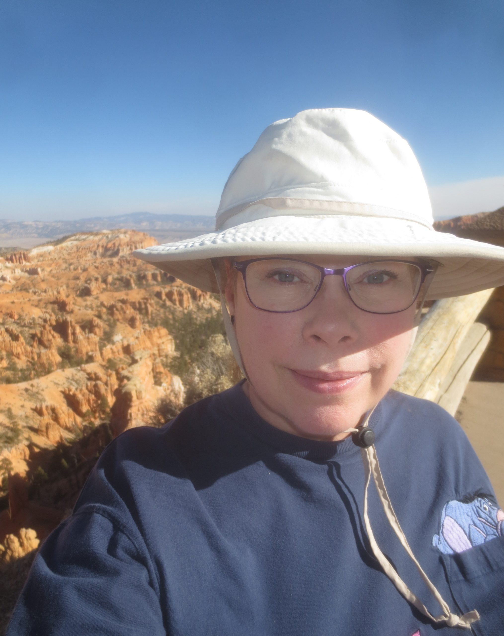 Woman in brimmed hiking hat standing next to fence along dropoff at Bryce Canyon Utah