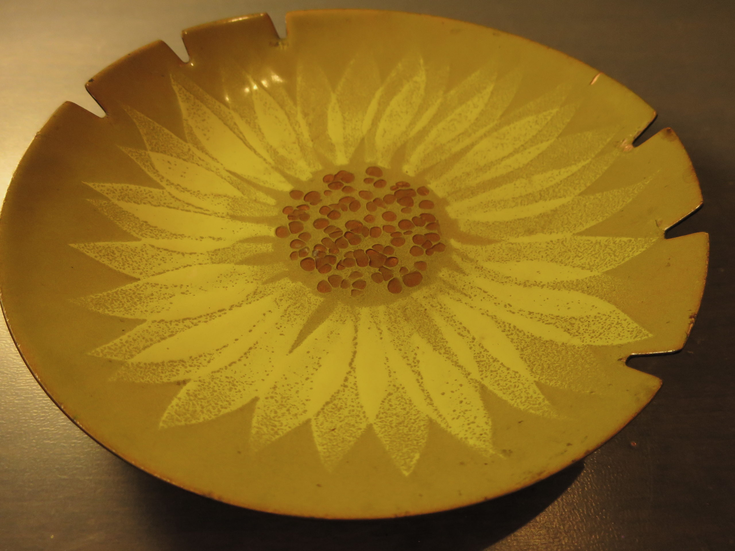 large round enamel ashtray with sunflower design in shades of yellow and orange