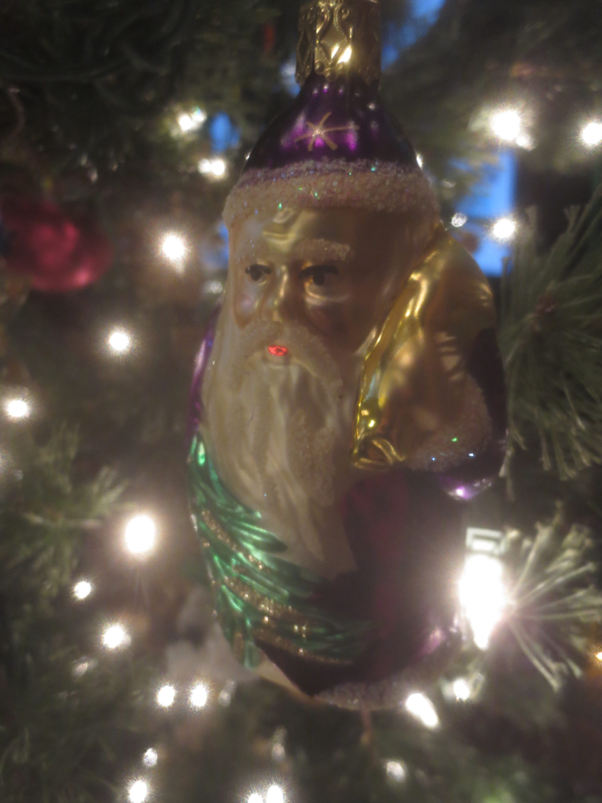 close up of a glass Santa ornament with a purple suit