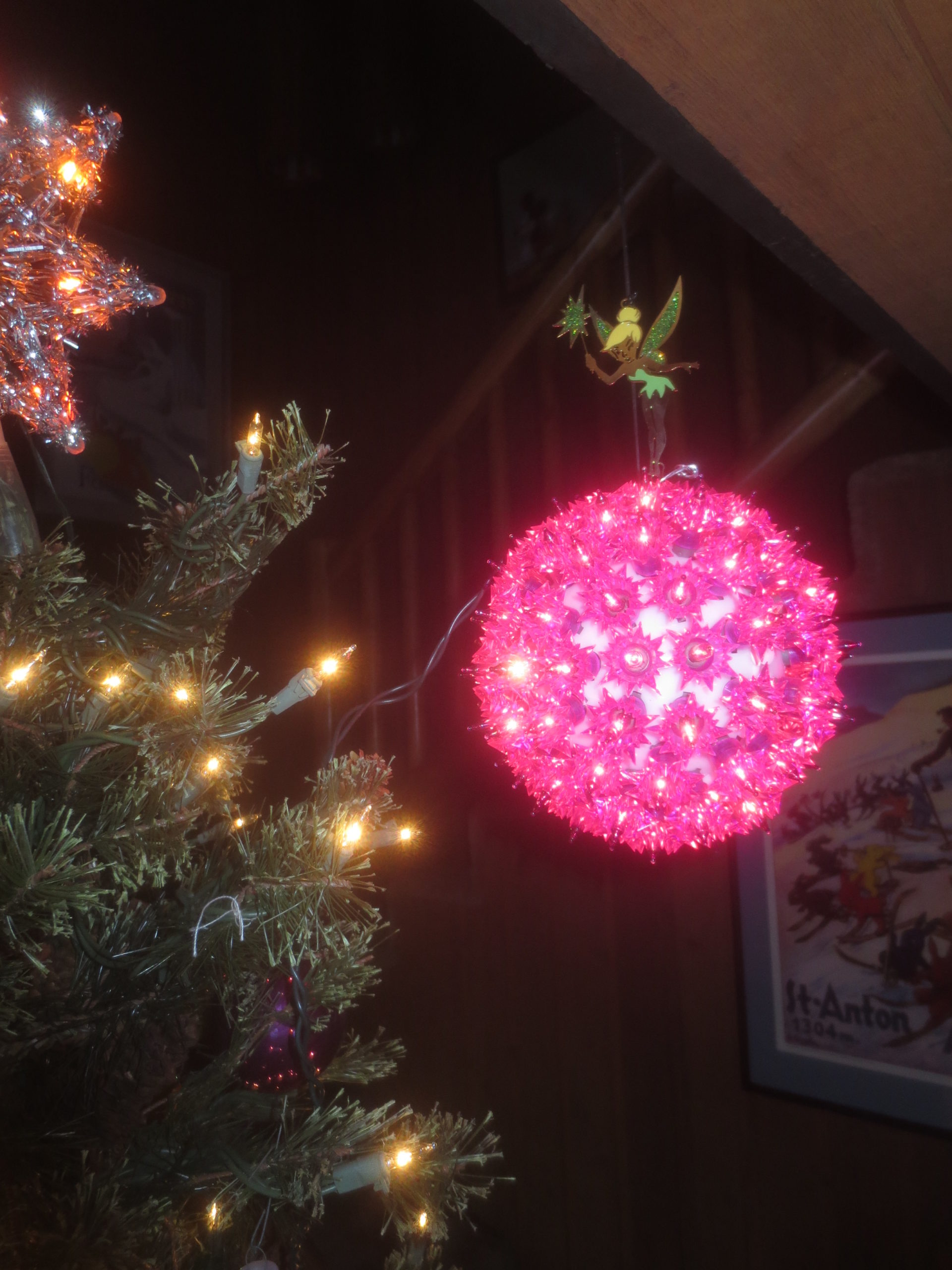 ball with purple Christmas lights topped by a Tinkerbell ornament
