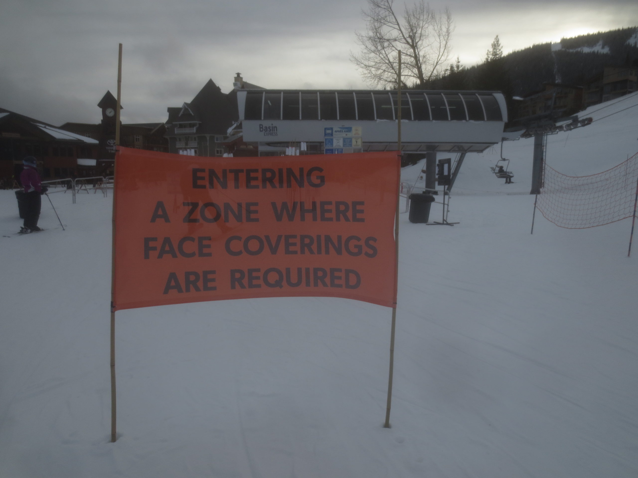 sign near a ski lift saying entering a zone where face coverings are required
