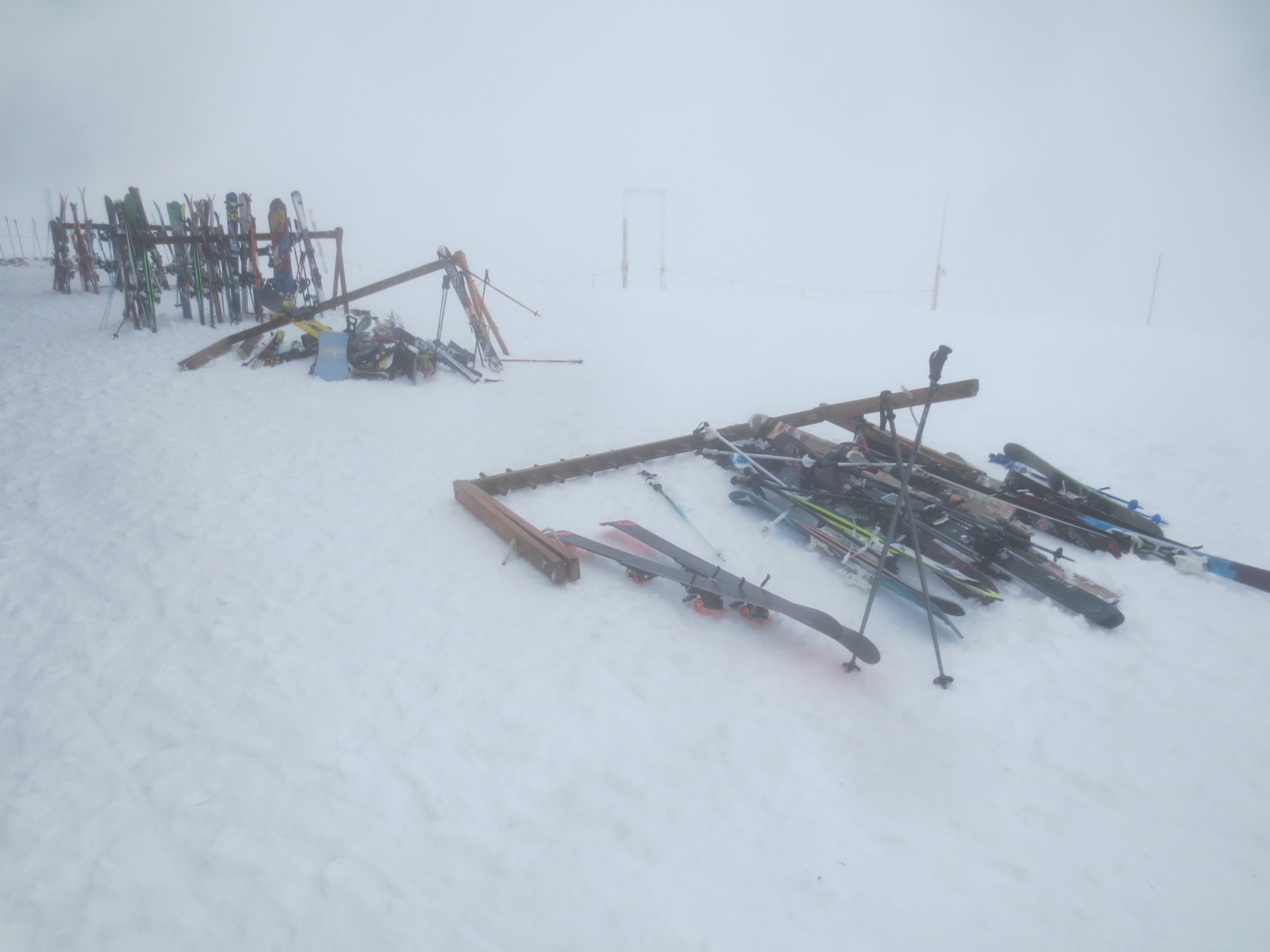 ski racks in the snow, with the two in the foreground blown over onto the ground